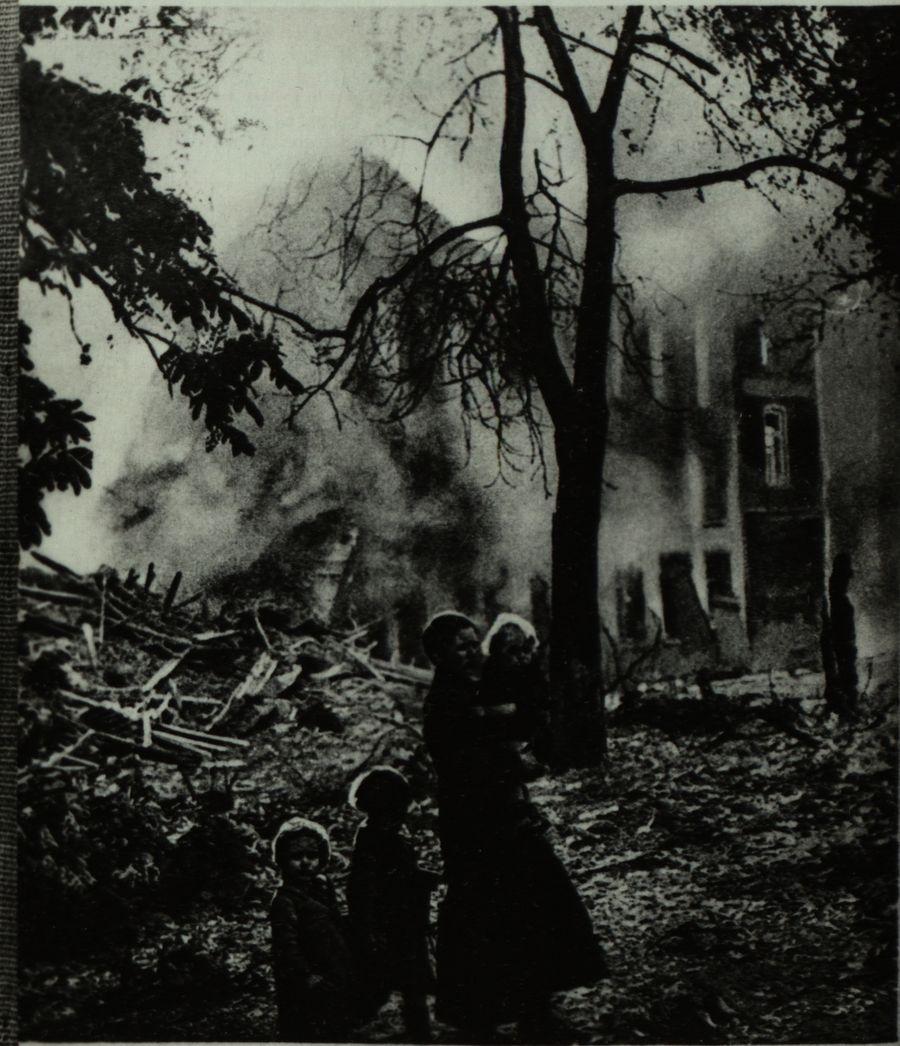 Matka z dziećmi na tle płonącego budynku