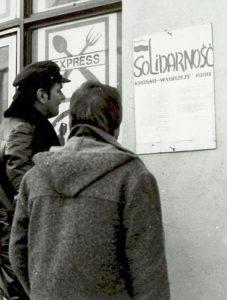 Zdjęcie dwóch mężczyzn, którzy czytają ogłoszenie zatytułowane Solidarność Krosno-Wybrzeże 1980 - wywieszone na ścianie budynku