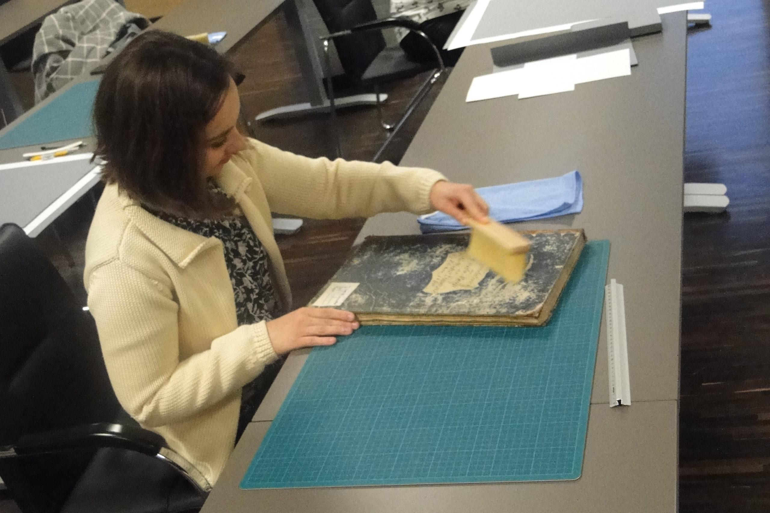 Kobieta odnawiająca stare akta siedzacza przy stole