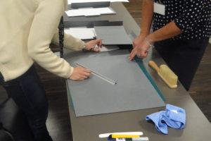 Konserwator pomaga uczestnikowi przygotować obwolutę ochronnąbrak