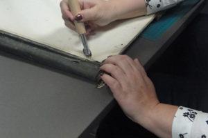 Uczestniczka warsztatów prostuje kauterem zagięte rogi dokumentówbrak