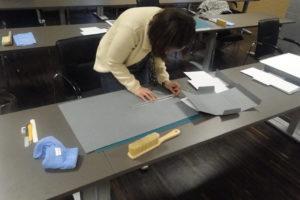 Uczestniczka warsztatów przygotowuje teczkę ochronną na książkębrak
